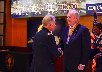 Colonel (Retired) Christopher St John '74 receives his medal from General Raymond Thomas III.