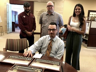 Jordan Haddock '18, Stafford Toone '18 and Daisy Claros '18 represent their fellow former students as Dr. Nicholas Conway '16 orders his Aggie Ring.