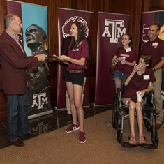 Texas A&M University President Michael K. Young hands a letter of admission to Ansley Herrin '23 as her sister, Ashlen, father, Scott '99, and mother Alicen '95 beam. Photos by Richard Badillo