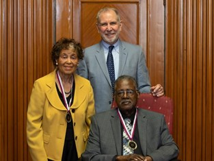 Wearing the Pioneer Medals are Katie Francis Johnson, who accepted on behalf of her late husband, Dr. James Johnson '67, and Leroy Sterling '67; they received the honor from A&M President Michael K. Young.